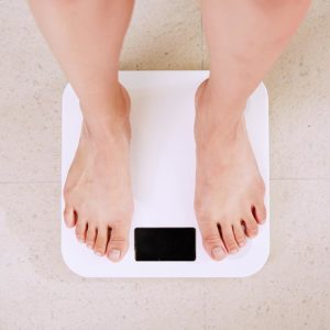 Person standing on a weighing scale.